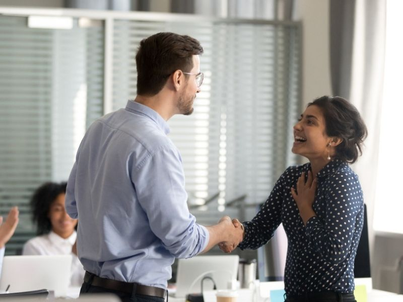 boss congratulating employee while colleagues applaud