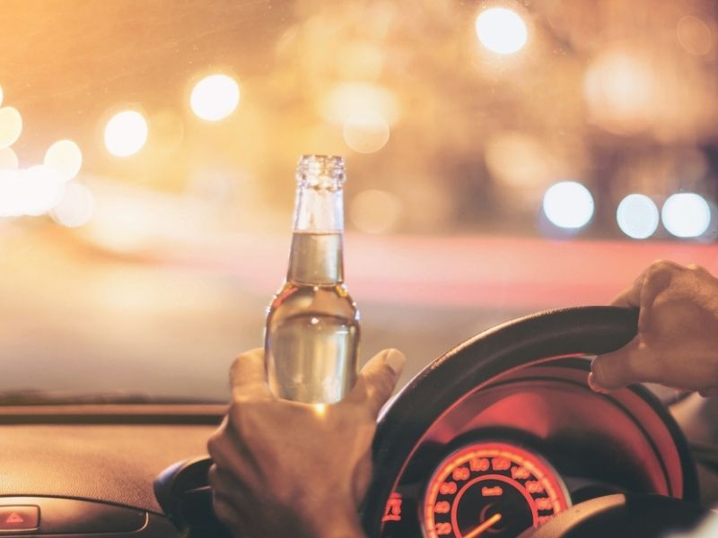 person driving a car with bottle of beer in hand